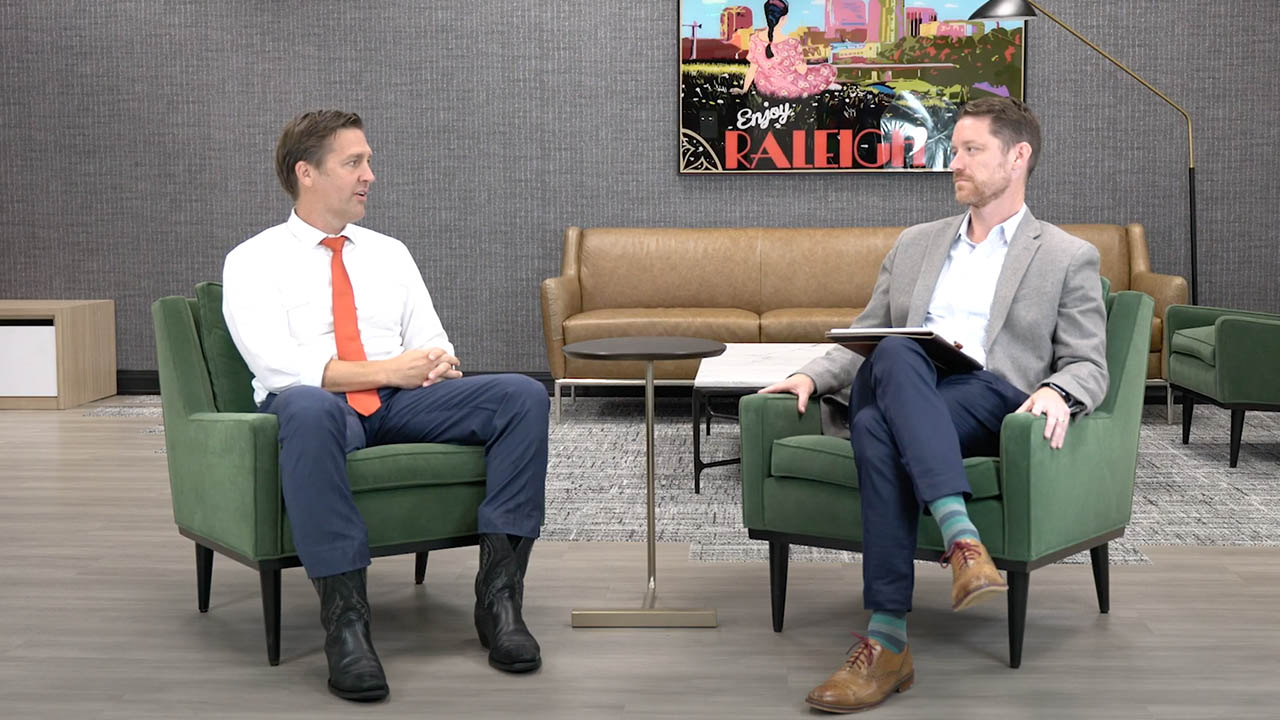 Senator Ben Sasse and Josh Chatraw sitting in green chairs having a conversation